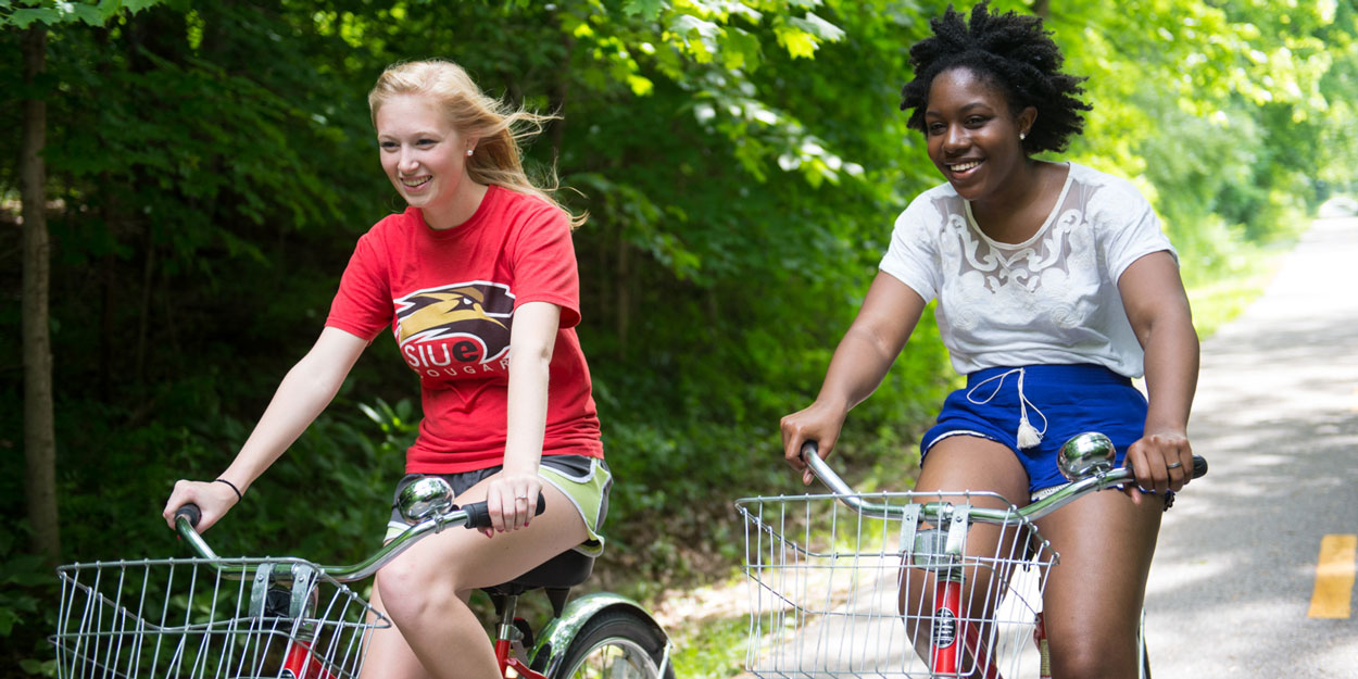 Two students riding bikes at SIUE.