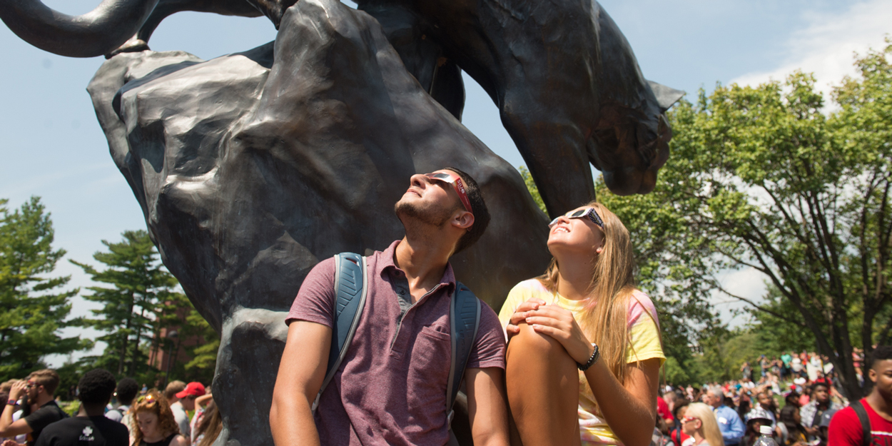 Two SIUE students looking at the sun during a solar eclipse next to the cougar statue outside of the Morris University Center.