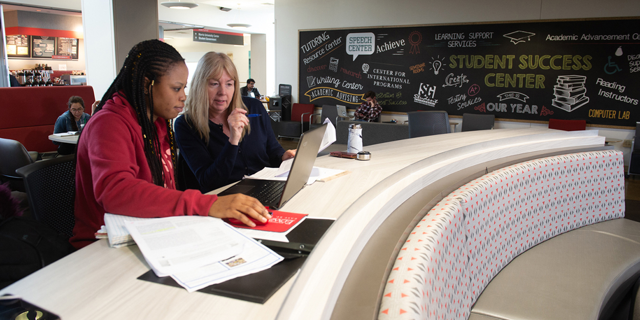 Two women talking in the Student Success Center at SIUE.