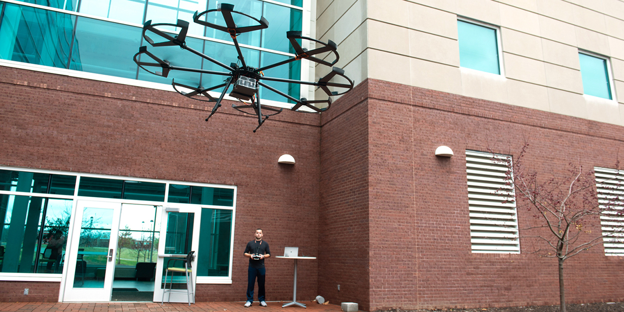 A student flying a drone outside of the Engineering Building at SIUE.