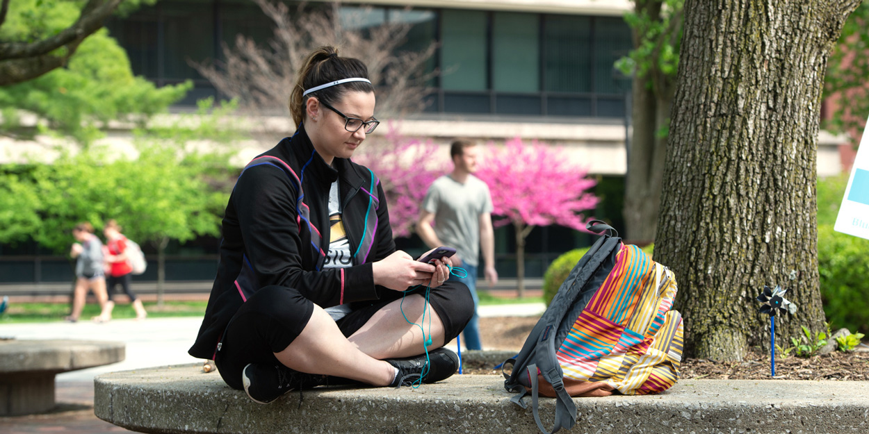 A student sitting on the Stratton Quadrangle at SIUE.