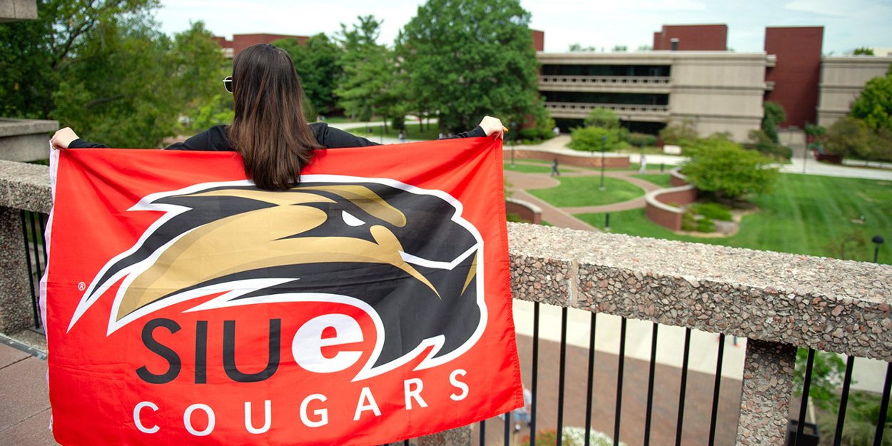 Female student holding a SIUE Cougar flag while standing on the second floor balcony of Rendleman Hall.
