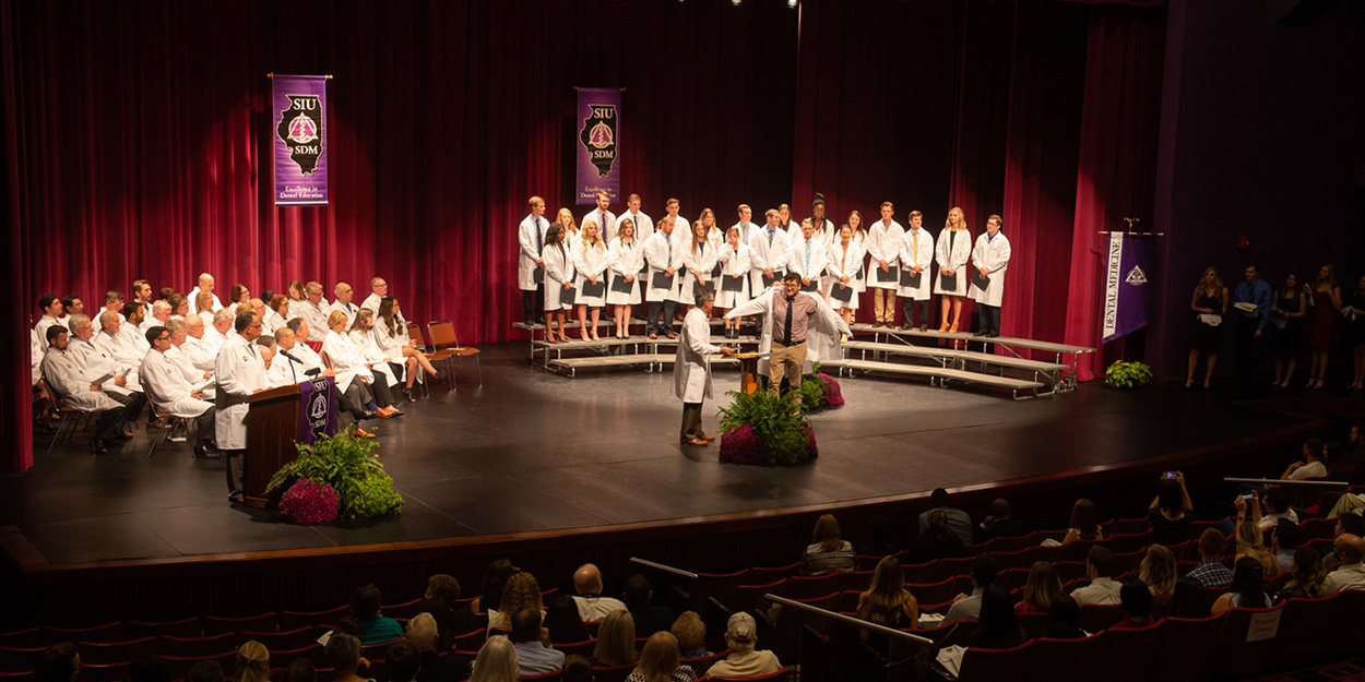 Student receiving there white coats.