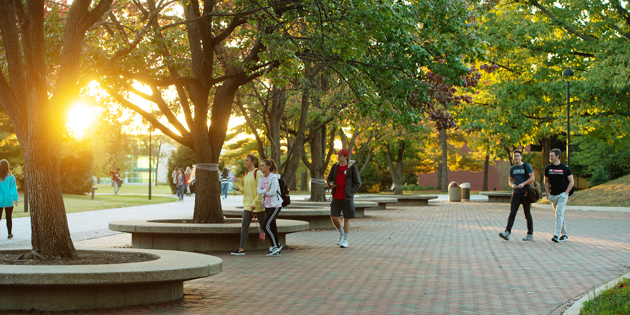Students walking on the SIUE campus at sunset.