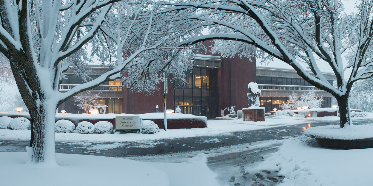 The front of the Morris University Center during the winter covered in snow.