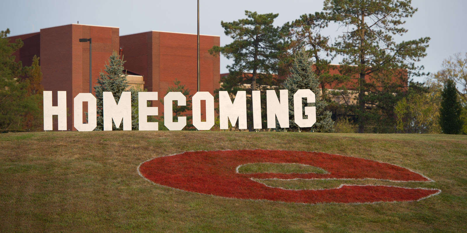 SIUE Homecoming sign on a hill in front of the Morris University Center during the morning.