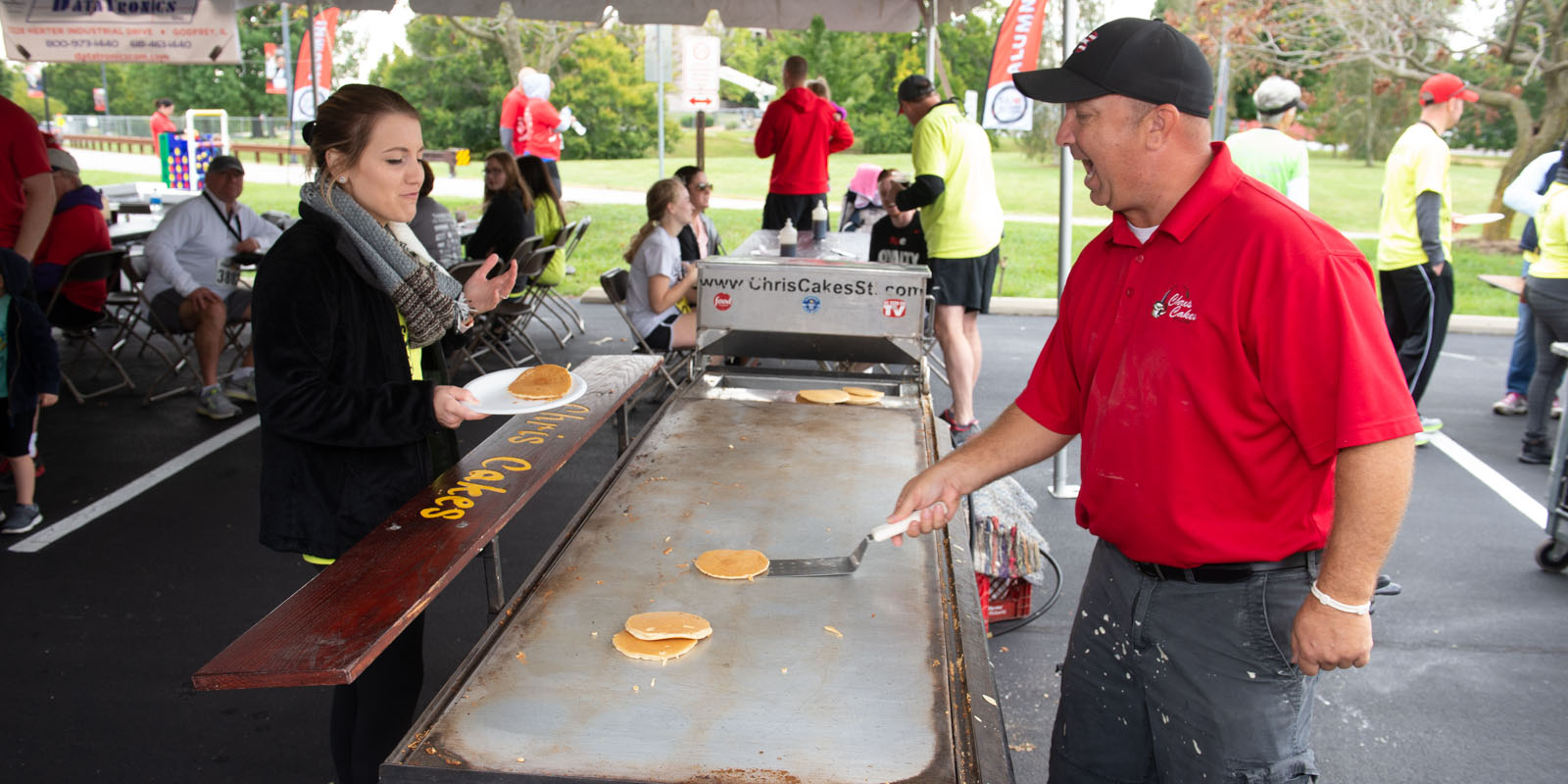 Man serving pancakes to a woman on a large grill.