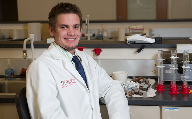 An alumni of the SIUE School of Pharmacy sitting in front of a lab table