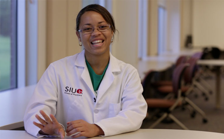 A student of the SIUE School of Pharmacy sitting at a table smiling