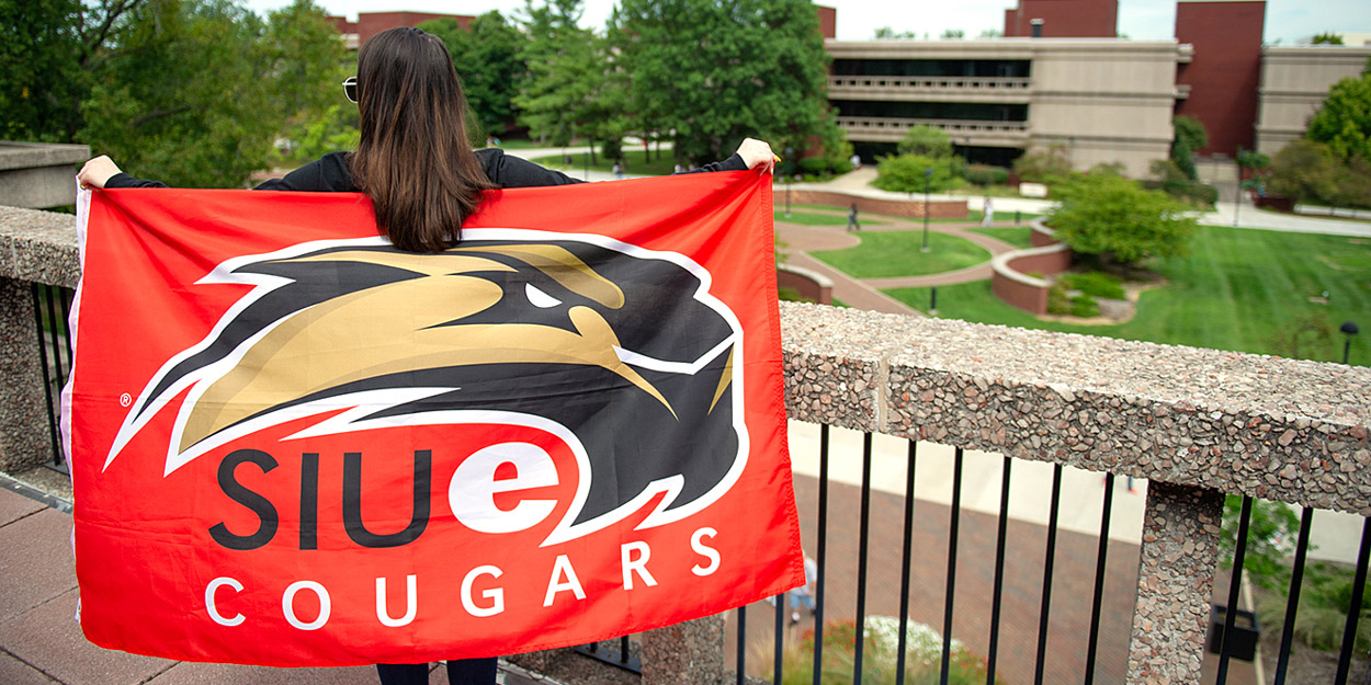 Student holding an SIUE flag while standing on the 3rd floor balcony of Rendleman Hall.