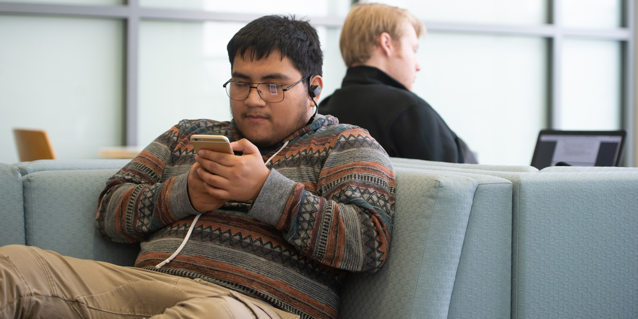 A student looking at his phone in the Student Success Center.