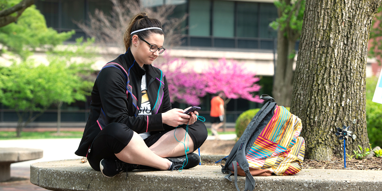 SIUE Student looking at her phone on the Stratton Quadrangle.