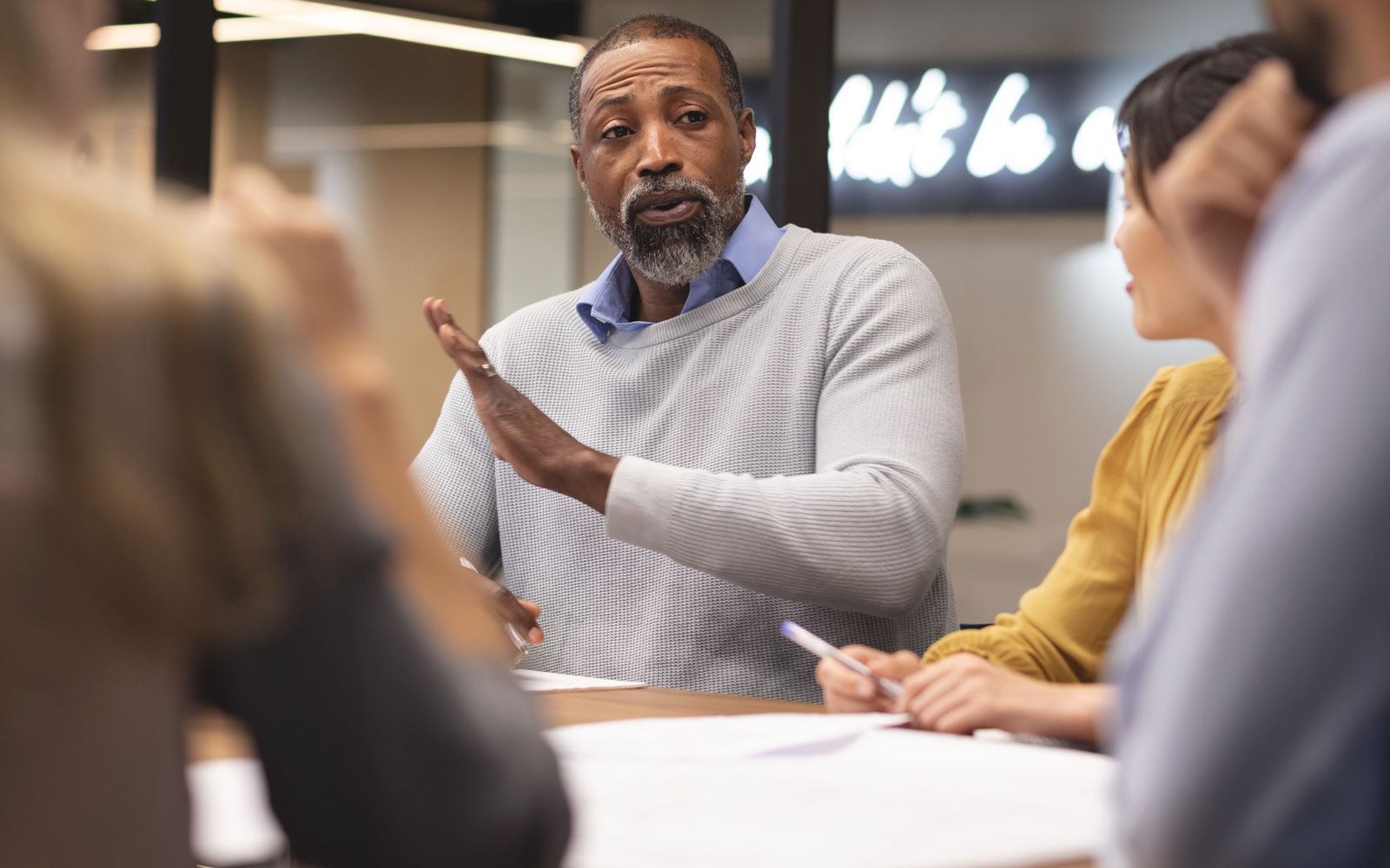 mature man at conference table with coworkers