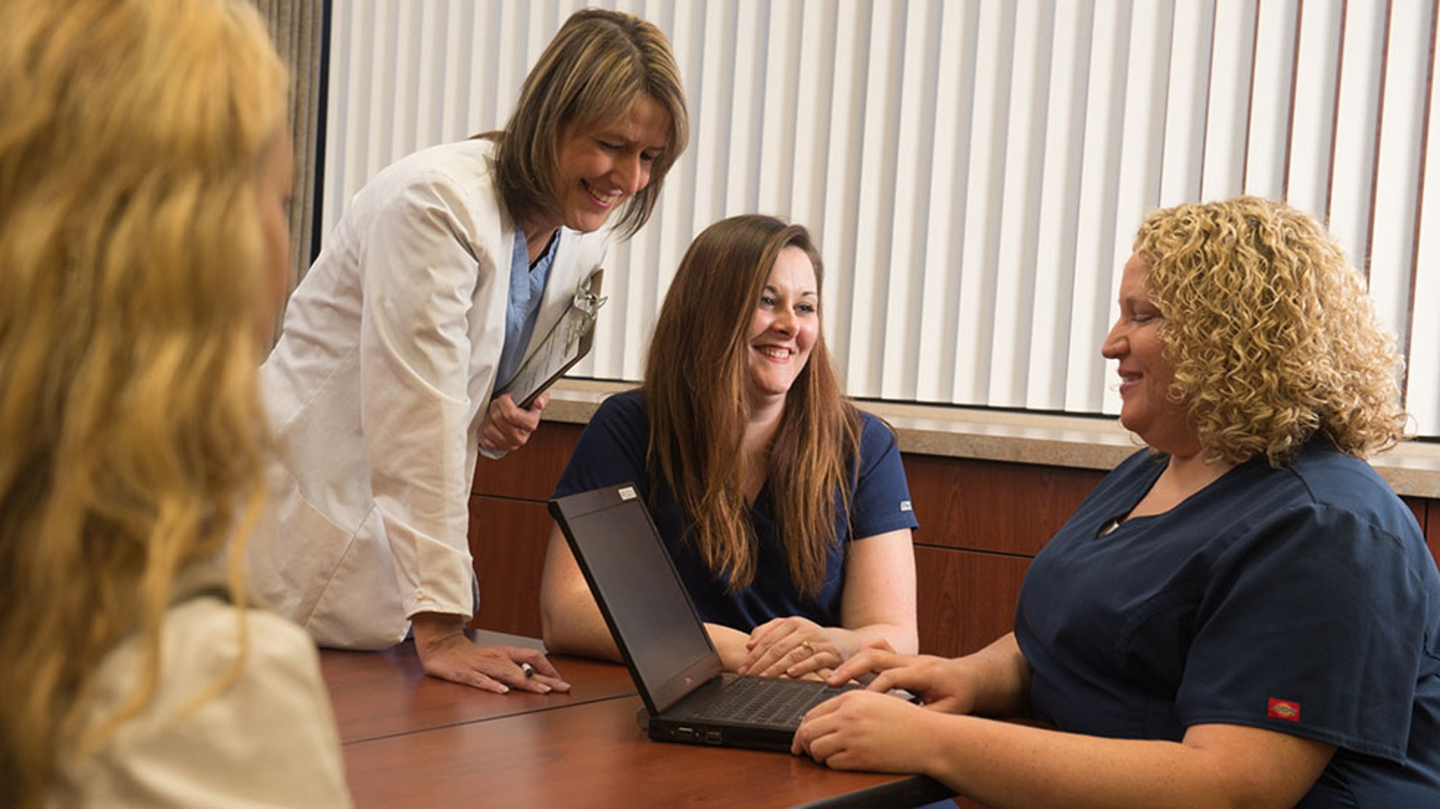 nurses smiling each other while looking at a laptop