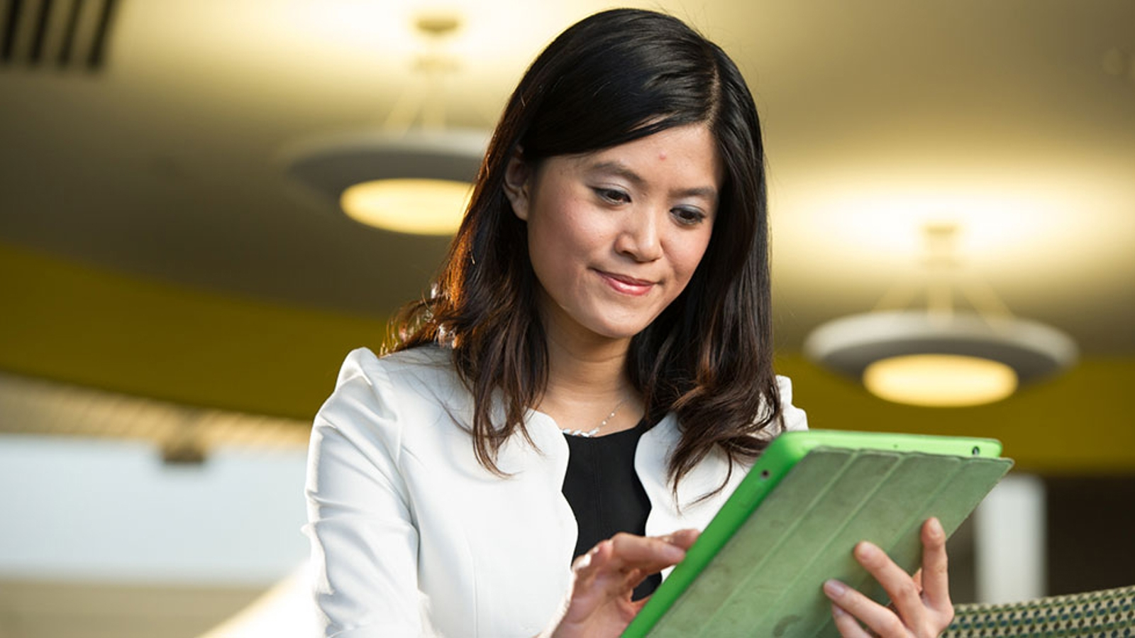 smiling female student studying on tablet