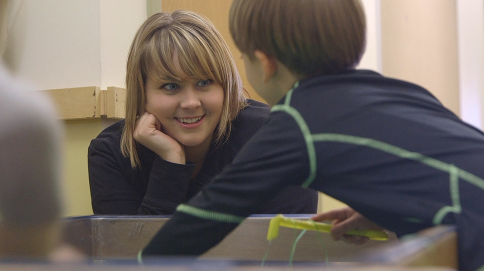 student teacher working with child in classroom