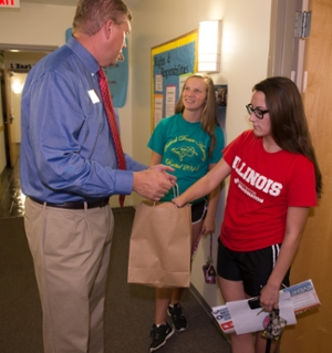 Vice Chancellor for Student Affairs Jeffrey Waple greets and offers candy to Jill Crabtree, a freshman majoring in marketing, and Maddie Barra, freshman psychology major, both from Pekin, Illinois.