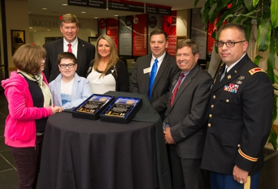 The Tipton family, Kaitlyn, Austin and Susie, pose with (L-R) SIUE's Jeffrey Waple, John Navin, Stephen Hansen, and Lt. Col. Scott Reed.