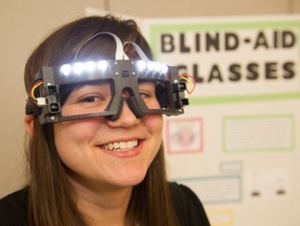 Hayley Day, a senior majoring in electrical engineering, demonstrates her research team's Blind-Aid Glasses.