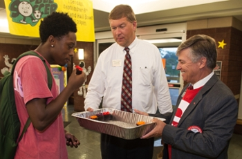 Javon Williams, of St. Louis, receives a sweet treat from Vice Chancellor for Student Affairs Jeffrey Waple (middle) and Chancellor Dr. Randy Pembrook during the annual House Calls event.