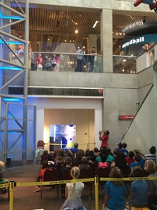 Noyce intern and SIUE sophomore Christian Watts leads a science show for a large group of visitors at the St. Louis Science Center.