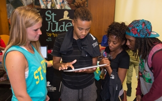 Student Leslie Hardin signs up to learn more information about St. Jude Up 'til Dawn. Looking on are fellow students (L-R) Kayley Stock, executive board member, and Taylor Sallis and Daniel Sims.