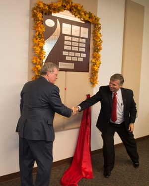 Chris Smith, president and CEO of H.D. Smith and current chair of the School's Pharmacy Advisory Board, and SIUE Chancellor Dr. Randy Pembrook, shake hands after unveiling the leadership wall.