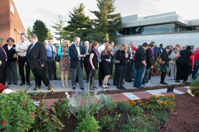 A crowd of attendees appreciates the newly-installed paver pathway at the School of Pharmacy's Medicinal Garden.
