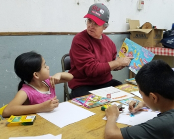 SIUE Chancellor Dr. Randy Pembrook reads to a small group of children during his service trip to Costa Rica.