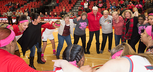 Breast cancer survivors join the SIUE women's basketball team in celebration ahead of the game against Jacksonville State.