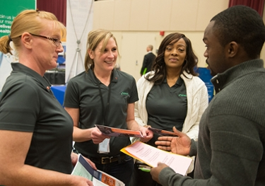 Representatives from Patheon, including two SIUE alumni, speak with a current student during the spring career fair.