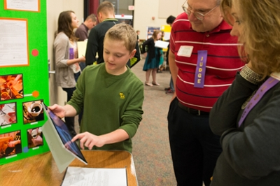 A student presents his STEM-focused project to a pair of judges during the Science Engineering Research Challenge held at SIUE.