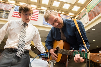 Nicholas Carter, of St. Charles, Mo., and Dan Ashbaugh, of Altamont, demonstrate the usability of their team's LED Learning Guitar.