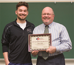SIU SDM Dean Dr. Bruce Rotter (R) presents the Oral Health Foundation Pierre Fauchard Academy Scholarship for 2017 to third-year student Kevin Wolf (L).