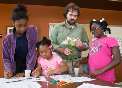 Colin Wilson with the SIUE STEM Center presents a lesson on hand pollinators as part of the Madison County Housing Authority's afterschool programming. Participating in the lesson are (L-R) Malia King, Taylor Ware and Wilniah Taylor.