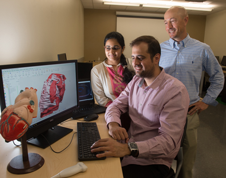 Graduate student Saygin Sop (seated) looks at a 3D model with fellow student Akhila Karlapalem, while Dr. Jon Klingensmith looks on.
