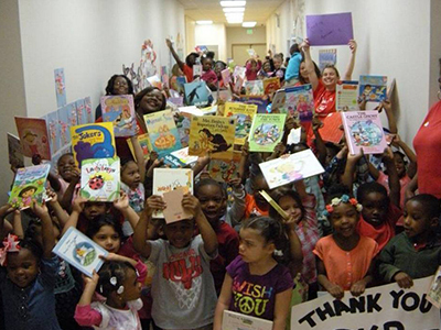 Children in the SIUE Head Start/Early Head Start Program happily display books that have been donated to them.