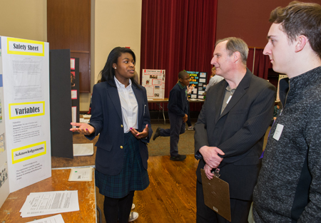 Breanna Goyea, a sophomore at Governor French Academy in Belleville, presents her research to two judges during the Science and Engineering Research Challenge at SIUE.