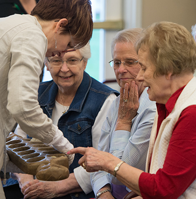 University Museum Collections Manager Erin Vigneau-Dimick shows Meridian Village residents artifacts from its collection. The featured residents include Dorothy Kueper, Joan Meier and Alice Mueller.