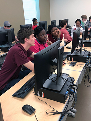 SIUE computer science student Eli Ball assists high school participants at the WeCode event.