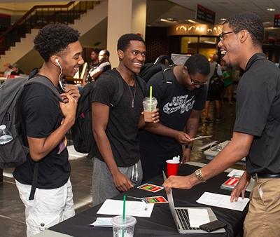(L-R) Sophomore Vernon Smith, freshman Karriem Muhammad, and sophomore Jeremiah Ratfliff gain information on Collegiate 100 president Braxton McCarroll.