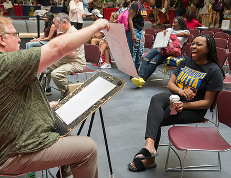 Capri Wroten, of Chicago, reacts happily to her newly created caricature during the SIUE Resource Fair.