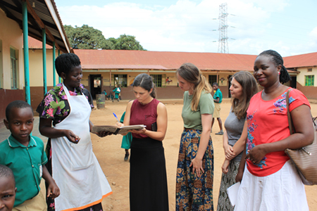 SIUE speech language pathology students Brianna Bowles, Sarah Geatley and Katherine Wilson, and Ugandan colleague Deborah Zawedde, signing the visitor's register at a primary school in Seeta, Uganda.