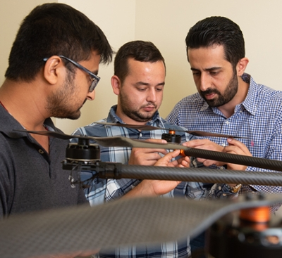 SIUE School of Engineering's Nima Lotfi, PhD, (back) and his students Nedret Ramic (middle), a mechanical engineering graduate student, and Pratik Lamsal, a senior mechanical engineering major, assemble a large drone.