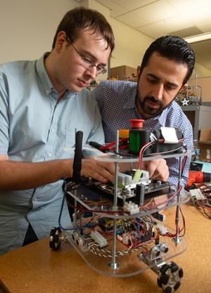 SIUE's Nima Lotfi, PhD, looks on as junior computer science major Jacob Novosad works on a robot in the mechatronics and robotics lab.