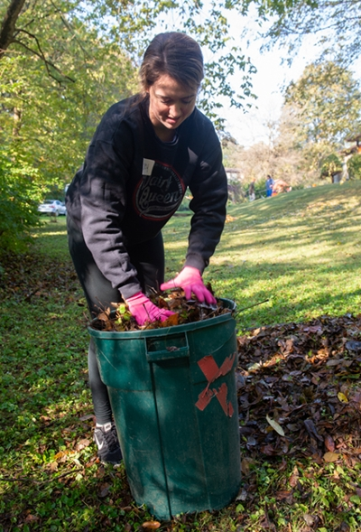 P1 student Lesley Swick loads a can full of leaves in an Edwardsville yard.