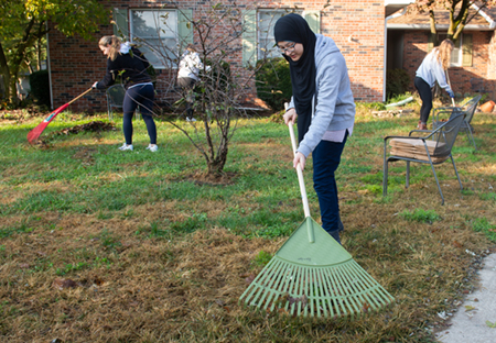 SIUE student Mariyam Alnoor helps rake the yard at a local residence.