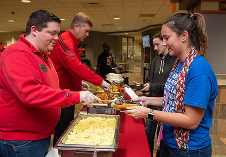 (L-R) SIUE's Tyler Manning and Jeffrey Waple serve breakfast to Amanda Vanderhaeghen, of Batavia, and Jessica Coats, of Normal.