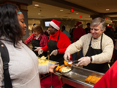 SIUE Chancellor Randy Pembrook serves hash browns to junior Eniola Awoniyi, of Chicago, during the annual Late Night Breakfast event.
