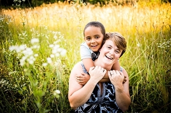 "Smiling brightly with her son is SIUE's Anni Reinking, EdD, assistant professor in the School of Education, Health and Human Behavior's Department of Teaching and Learning, and author of ""Not Just Black and White."""